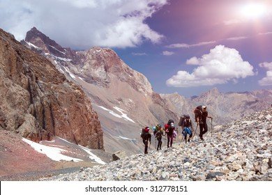 Group of Mountaineer Walking on Deserted Rocky Terrain Five Members Team Sport Clothing Going Heavy Load Backpacks Climbing Gear Up  Mountain Peaks Blue Sky Majestic Summits Shining Sun Background