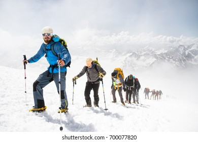 A group of mountaineers climbs to the top of a snow-capped mountain