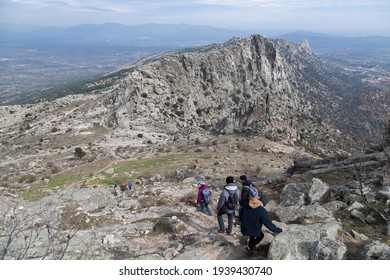 Group of mountaineers descends a rocky granite mountain in the north of Madrid, Spain.