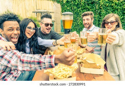 Group of mult-ethnic friends toasting beer glasses - Happy people partying and eating in home garden - Young active adults in a picnic area with burgers and drinks