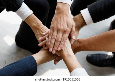 Group of multi colors hands stack together and smiling in the symbol of unity and strong teamwork.