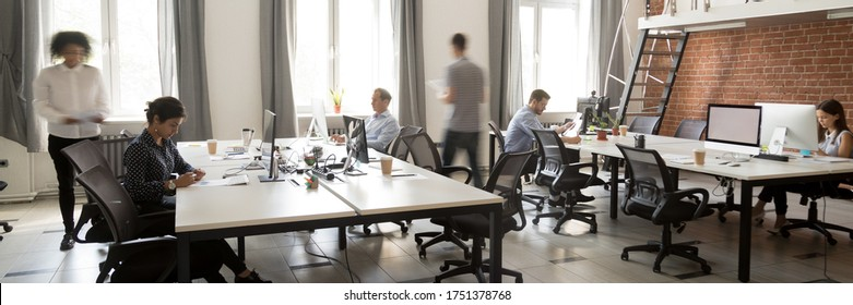 Group of multi ethnic corporate employees working in co-working open space walking in motion, sit at shared desks. Busy workday, office rush concept. Horizontal photo banner for website header design
