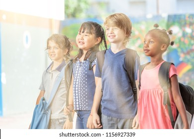 Group of multi ethnic elementary classmates happy in schoolyard, sun rays coming from the sky.