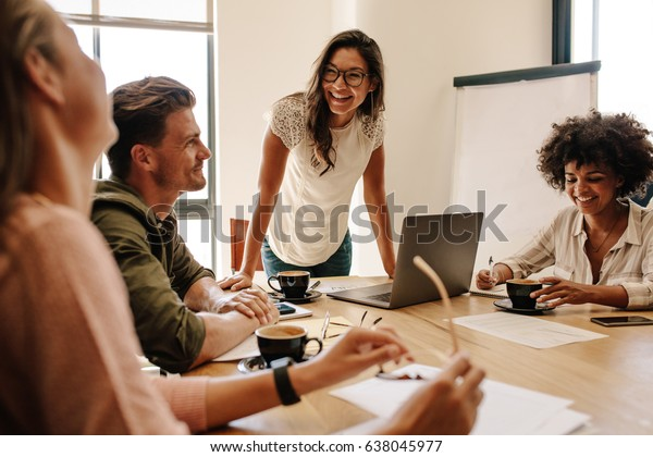 Group of multi ethnic executives discussing during a meeting. Business man and woman sitting around table at office and smiling.
