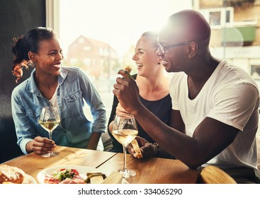 Group of multi ethnic friends drinking wine at a cafe outside