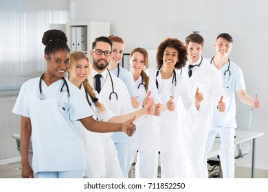 Group Of Multi Ethnic Male And Female Doctors Showing Thumb Up Sign In Clinic