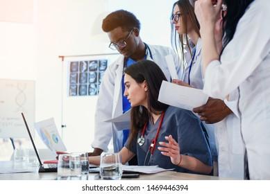 Gruppe multiethnischer Fachärzte, die Laptop benutzen, um die Probleme der Patienten im Konferenzraum im Krankenhaus zu diskutieren. Konzept der Medizin und des Gesundheitswesens.