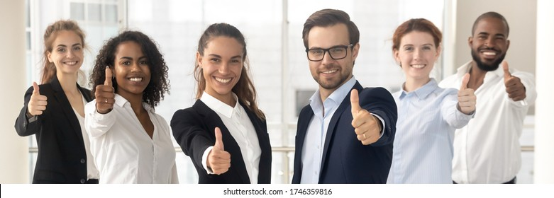 Group of multi ethnic staff standing in row smiling showing thumbs up hand gesture, concept of career success growth, best corporate service feedback. Horizontal photo banner for website header design