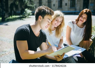Group of multi ethnic students study in a city park . Preparing for exam on a fresh air.