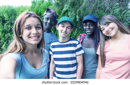Group of multi ethnic teenagers outdoor making selfies.