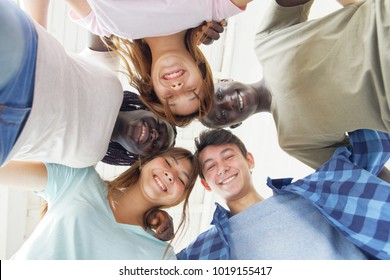 Group of multi ethnic teenagers smiling downward to camera.