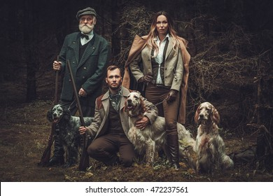 Group of multi-age hunters with dogs and shotguns in a traditional shooting clothing on a dark forest background.