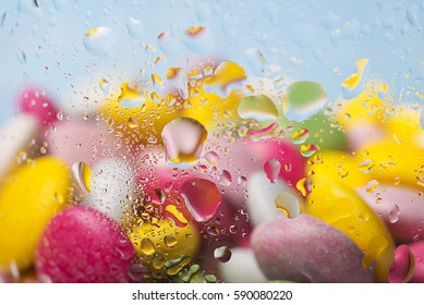 Group of multicolored sweets , through glass with drops of water
