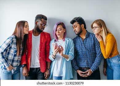 Group Multicoloured People standing against white wall. Caucasian woman with pink hair showing photos on smartphone to her diverse friends. Technology concept with young users people.