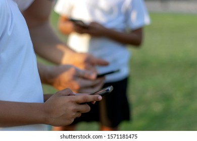 Group of multicultural boys using smartphone outdoors.Unrecognized people hands addicted by mobile mobile.Shot of unidentifiable friends using their phones together.Three friends using mobile device.