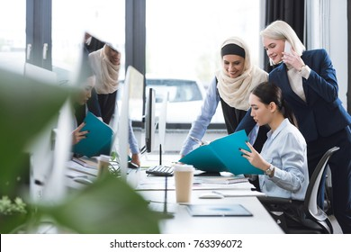 group of multicultural businesswomen discussing new project at workplace in office
