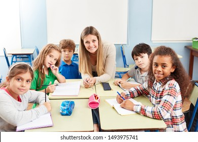 Group of multicultural elementary students in tutoring lessons with teacher