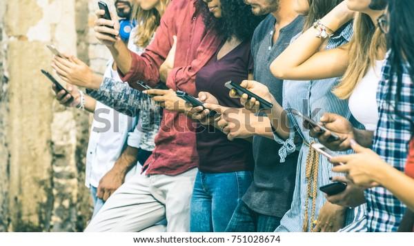 Skupina multikulturních přátel pomocí smartphone venku - Lidé ruce závislý mobilní chytrý telefon - Technologický koncept s připojenými muži a ženami - Mělká hloubka ostrosti na vintage filtrační tón