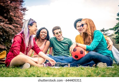 Group of multicultural people having fun while bonding in a park outdoors