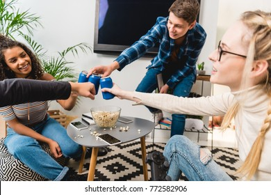 group of multicultural teens clinking with cans