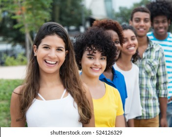 Group of multicultural young adults in a row outdoor in the city in the summer