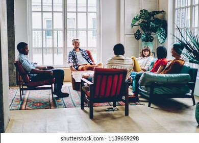 Group of multicultural young people resting in comfortable hostel and playing game in free time.Diverse hipster friends enjoying communication with each other sitting in modern apartment