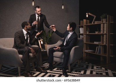 group of multiethic businessmen relaxing and drinking alcohol