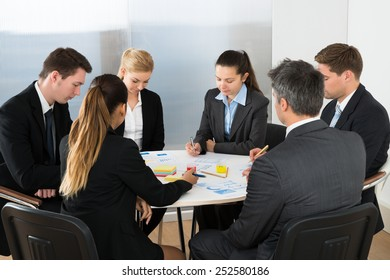 Group Of Multiethnic Businesspeople Analyzing Graph In Office