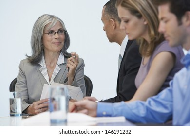 Group of multiethnic businesspeople sitting at conference table