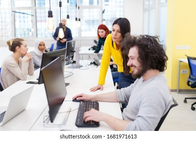 Group of multiethnic colleagues working on desktop computers in a modern office space.