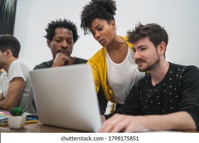 Group of multiethnic creative business people working on a project. Business woman pointing at the monitor screen and showing something to her colleagues. Business concept.