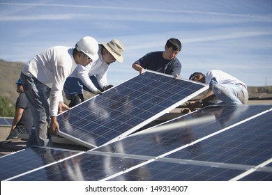 Group of multiethnic engineers placing solar panels on rooftop