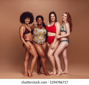 Group of multi-ethnic female with different figure and size in bikinis over brown background. Full length of multiracial women in swimsuit looking at camera and smiling.