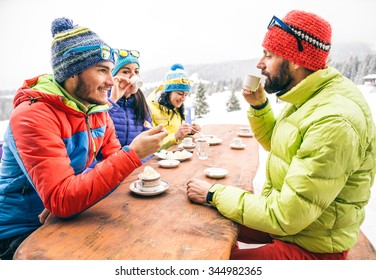 Group of multi-ethnic friends drinking hot chocolate and coffee - Happy people partying and eating in home garden - Young active adults in a restaurant on winter vacation
