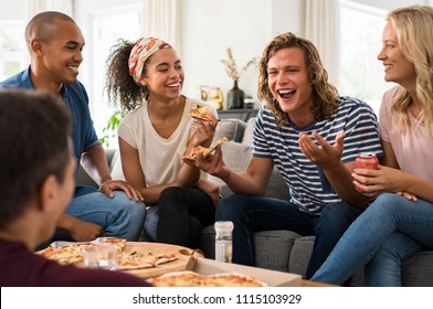 Group of multiethnic friends eating pizza during party at home. Group of young men and women having fun together. Happy people talking and laughing while eating italian food and sitting on couch.