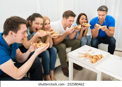 Group Of Multiethnic Friends Eating Pizza Together