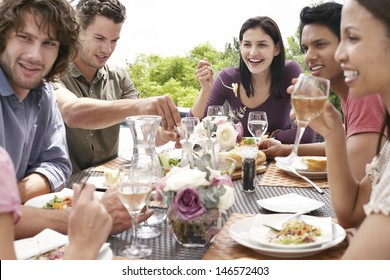 Group of multiethnic friends enjoying dinner party outdoors