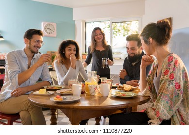 A group of multi-ethnic friends gathered around a table in the kitchen for breakfast