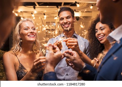 Group of multiethnic friends having fun with sparkling sticks during night party. Group of elegant women and men holding sparklers and celebrating the new year's eve.