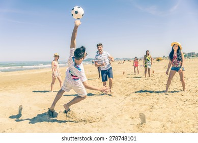 Group of multiethnic friends playing soccer on the beach - Football match on the sand on summertime - Tourists having fun on vacation with beach games