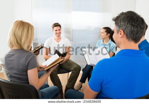 Gruppe multiethnischer Freunde, die Bibel gemeinsam lesen