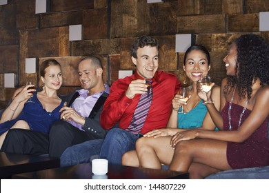 Group of multiethnic friends sitting on couch with drinks in bar