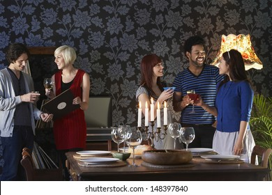 Group of multiethnic friends smiling by dining table