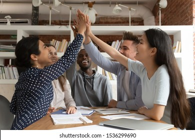 Group of multi-ethnic friends students sit at desk celebrating graduation or team achievements give high five stack palms raise hands together feels excited, successful study, unity support concept