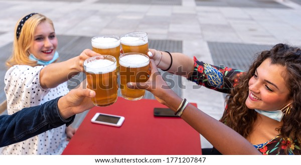 group of multi-ethnic friends toast raising glasses of beer, focus on the four raised beers and the hands of millenials toasting, blonde girl and curly brunette in the background