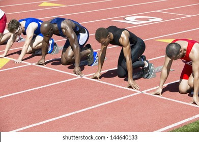 Group of multiethnic male athletics waiting at starting blocks