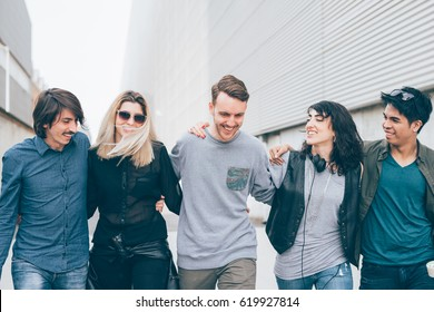 Group of multiethnic millenial friends  walking arm around outdoor having fun - togetherness, happiness, friendship concept