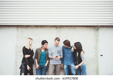 Group of multiethnic millennial friends outdoor using smart phone - technology, social network, togetherness concept