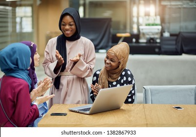 Group of multiethnic muslim young women dressed in smart colorful national wear resting in cafe, shopping on-line, using laptop computer