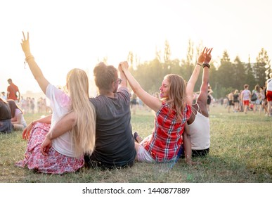 Group of multiethnic people sitting on grass ang having fun at summer music fetival